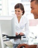 Zwei Kollegen, die an einem ihrem Computer arbeiten Lizenzfreies Stockfoto