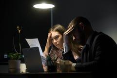 Zwei Kollegen, die schlechten Umgang betrachten, berichten in der Abendsitzung lizenzfreies stockfoto