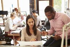 Zwei Kollegen, die am Schreibtisch mit Sitzung im Hintergrund arbeiten Lizenzfreies Stockfoto