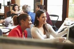 Zwei Kollegen, die am Schreibtisch mit Sitzung im Hintergrund arbeiten lizenzfreie stockfotografie