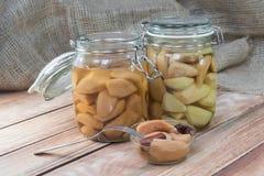 Zwei konservierten Birne im Glasgefäß auf Holztisch mit Birne Compot lizenzfreie stockfotografie