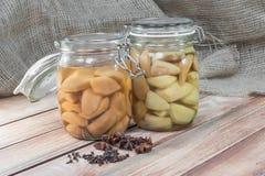 Zwei konservierten Birnen-Kompott im Glasgefäß auf Holztisch mit Sta lizenzfreie stockbilder
