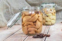 Zwei konservierten Birnen-Kompott im Glasgefäß auf Holztisch mit Sta lizenzfreie stockfotografie