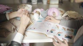 Zwei kreative Freundinnen, die Buch mit strickendem Muster verwenden Strickende Hände stock footage