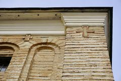 Zwei Kreuze auf Backsteinmauer gegen blauen Himmel Orthodoxes Kreuz Stockbild