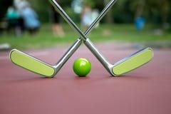 Zwei kreuzten minigolf Eisenschläger und einen grünen Ball an einem minigolf Stockfotografie