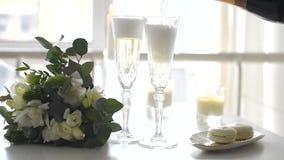 Zwei Kristallgläser des Champagners und des Hochzeitsblumenstraußes stock footage