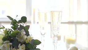 Zwei Kristallgläser des Champagners und des Hochzeitsblumenstraußes stock video