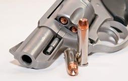 Zwei Kugeln vor einem geladenen Revolver stockbild