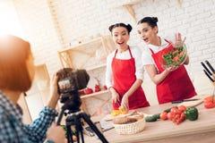 Zwei kulinarische Bloggers, die gewürfelte Pfeffer mit Salat zur Kamera mischen Lizenzfreies Stockfoto