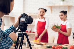 Zwei kulinarische Bloggers, die gewürfelte Pfeffer mit Salat zur Kamera mischen Lizenzfreie Stockbilder
