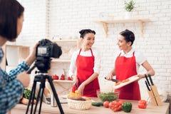 Zwei kulinarische Bloggers, die gewürfelte Pfeffer mit Salat zur Kamera mischen Lizenzfreies Stockbild