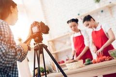 Zwei kulinarische Bloggers, die Pfeffer mit Messern zur Kamera würfeln Stockfotos