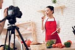 Zwei kulinarische Bloggers, die Salat mit einem Mädchen hinter Kamera schmecken Stockfotografie