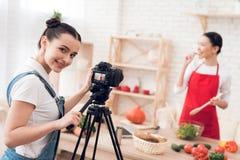Zwei kulinarische Bloggers, die Salat mit einem Mädchen hinter Kamera schmecken Stockbilder