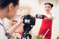 Zwei kulinarische Bloggers, die selfie mit einem Mädchen hinter Kamera nehmen Lizenzfreies Stockfoto