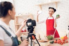 Zwei kulinarische Bloggers, die selfie mit einem Mädchen hinter Kamera nehmen Stockbilder