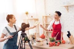 Zwei kulinarische Bloggers, die winewith eins Mädchen hinter Kamera schmecken Lizenzfreies Stockbild