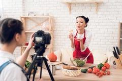 Zwei kulinarische Bloggers, die winewith eins Mädchen hinter Kamera schmecken Stockbild