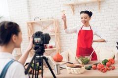 Zwei kulinarische Bloggers, die winewith eins Mädchen hinter Kamera schmecken Stockbilder