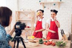 Zwei kulinarische Bloggers halten gewürfelte Pfeffer zur Kamera Lizenzfreie Stockfotos