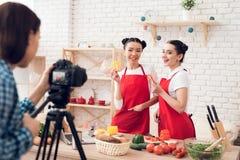 Zwei kulinarische Bloggers halten gewürfelte Pfeffer zur Kamera Stockbilder