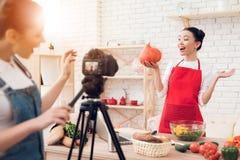 Zwei kulinarische Bloggers halten Kürbis mit einem Mädchen hinter Kamera Stockbilder