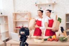 Zwei kulinarische Bloggers halten packagges mit Lebensmittel zur Kamera Lizenzfreie Stockfotos