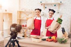 Zwei kulinarische Bloggers halten packagges mit Lebensmittel zur Kamera Lizenzfreie Stockfotografie