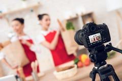 Zwei kulinarische Bloggers halten packagges mit Lebensmittel zur Kamera Stockfotografie