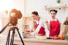 Zwei kulinarische Bloggers halten packagges mit Lebensmittellesung von Laptop zu Kamera Stockbild