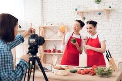 Zwei kulinarische Bloggers halten Pfeffer und Messer zur Kamera Lizenzfreie Stockfotos