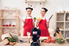 Zwei kulinarische Bloggers halten Pfeffer und Messer zur Kamera Lizenzfreie Stockbilder