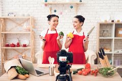 Zwei kulinarische Bloggers halten Pfeffer und Messer zur Kamera Stockbild