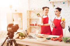 Zwei kulinarische Bloggers halten Pfeffer und Messer zur Kamera Stockfoto