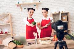 Zwei kulinarische Bloggers halten Pfeffer und Messer zur Kamera Stockbilder