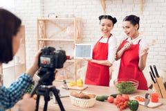 Zwei kulinarische Bloggers halten Tablette und Spachteln zur Kamera Stockfotografie