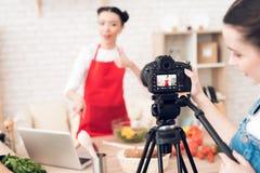 Zwei kulinarische Bloggers lasen vom Laptop mit einem Mädchen hinter Kamera Lizenzfreies Stockfoto