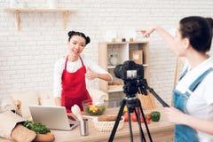 Zwei kulinarische Bloggers lasen vom Laptop mit einem Mädchen hinter Kamera Lizenzfreie Stockbilder