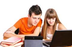 Zwei Kursteilnehmer, die mit Büchern und Laptop erlernen Stockbilder