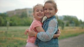 Zwei lächelnd, gelockte, nette Schwesterbabys, fest zu umarmen Glückliche Kindheit, positive Gefühle, wahre Gefühle stock video footage