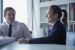 Zwei lächelnde Architekten, die über einem Plan im Büro sich besprechen, lizenzfreie stockbilder