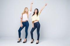 Zwei lächelnde attraktive Freundinnen blond und Brunetteaufstellung glücklich auf weißem Hintergrund Lizenzfreies Stockbild