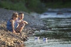 Zwei lächelnde blonde Kinder, Junge und Mädchen, die mit weißem pape spielen Stockbild
