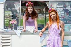 Zwei lächelnde Damen, die Weinlese tragen, kleidet mit Eiscremepackwagen an lizenzfreie stockfotos