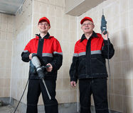 Zwei lächelnde Erbauer in den konstanten Holdinghilfsmitteln Lizenzfreie Stockfotografie