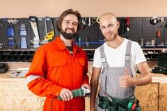 Zwei lächelnde Erbauer in der Arbeitskleidung, die glücklich in camera s schaut lizenzfreie stockfotos