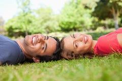 Zwei lächelnde Freunde, die in Richtung der Seite beim Lügen blicken Lizenzfreies Stockfoto