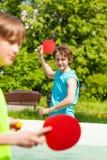 Zwei lächelnde Freunde, die zusammen Klingeln pong spielen Lizenzfreie Stockbilder