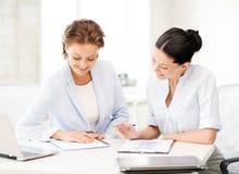 Zwei lächelnde Geschäftsfrauen, die im Büro arbeiten Stockfoto